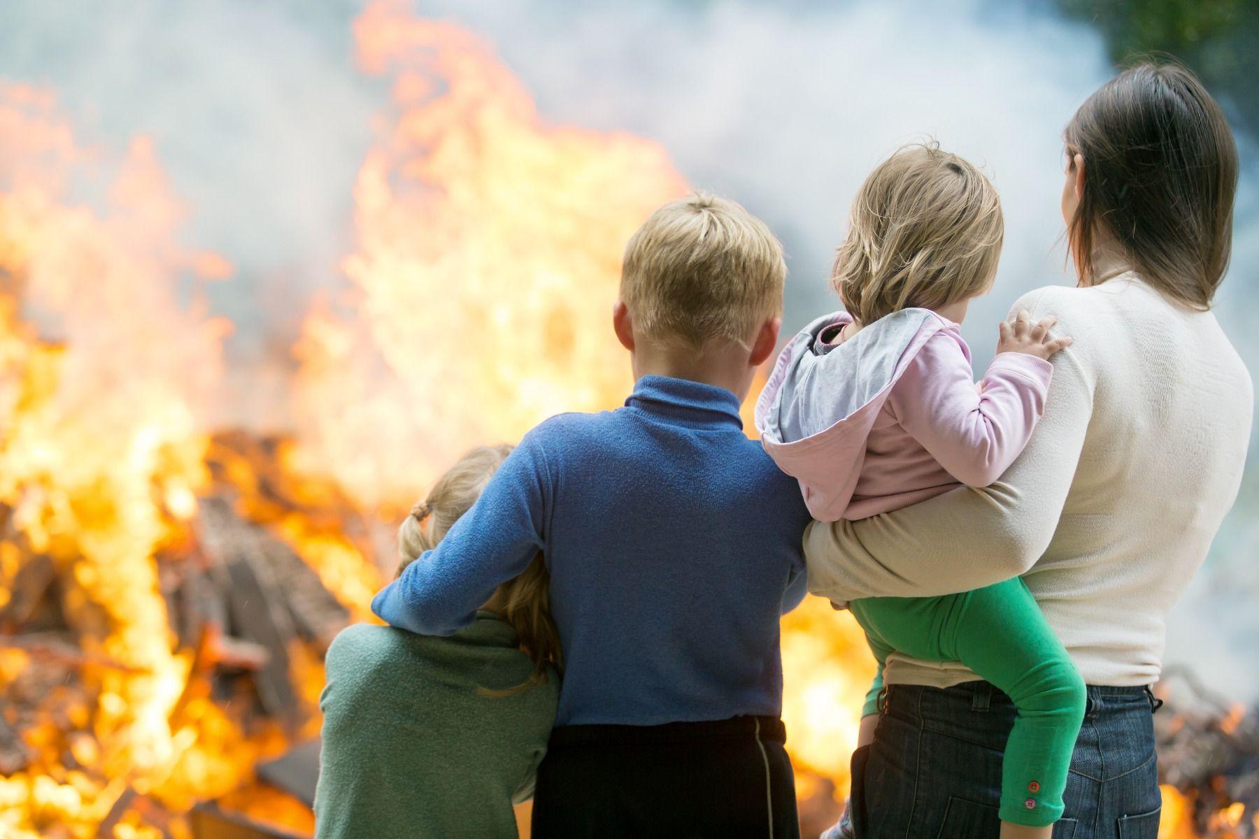 Brandgefahr Familie vor brennendem Haus
